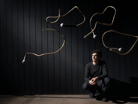 Microphones suspended in the air as artist Dylan Sheridan crouches on one knee