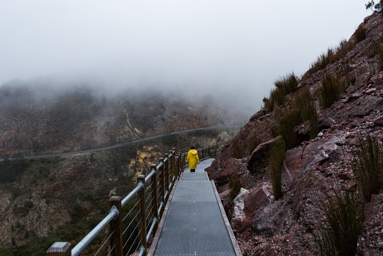 Person in yellow coat walking on a boardwalk next to a cliff. Foggy landscape and twisting road in the distance.
